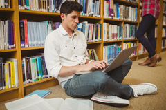 Male student working on floor. In library Royalty Free Stock Images
