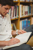 Male student working on floor. In library Royalty Free Stock Photos