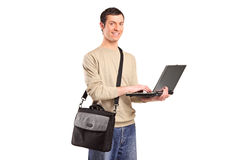 A male student working on a laptop. A portrait of a male student with a shoulder bag working on a laptop isolated on white background Stock Images