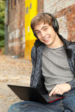 Male student working on laptop. Sitting near the wall Royalty Free Stock Images