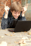 Male student working on laptop. Lying near the wall Stock Photo