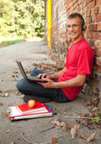 Male student working on laptop. Sitting near the wall Royalty Free Stock Image