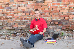 Male student working on laptop. Leaning on the bricks wall Royalty Free Stock Photos