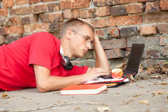 Male student working on laptop. Lying near the wall Royalty Free Stock Images