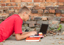 Male student working on laptop. Lying near the wall Stock Image