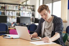 Male Student Working At Laptop In College Library Stock Image