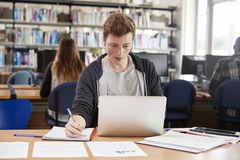 Male Student Working At Laptop In College Library Stock Images