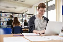 Male Student Working At Laptop In College Library Royalty Free Stock Image