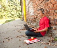 Male student working on laptop, outdoors. Male student working on laptop, sitting near the wall Royalty Free Stock Image