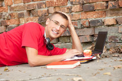 Male student working on laptop, outdoors. Male student working on laptop, lying near the wall Stock Photography