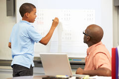 Male Student Writing Answer On Whiteboard. In Classroom Concentrating Royalty Free Stock Images