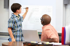 Male Student Writing Answer On Whiteboard. Standing Still Concentrating Royalty Free Stock Photo