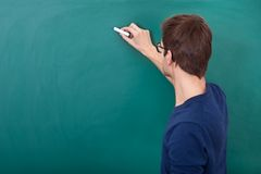 Male student writing on chalkboard. Rear View Of A Male Student Writing On Chalkboard With Chalk Stock Images