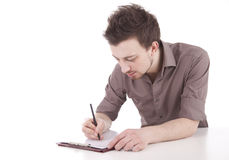 Male student writing on clipboard. Sitting at desk, white background Stock Image