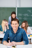 Male Student Writing With Female Classmates And Teacher In Backg Royalty Free Stock Images