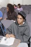 Male Student Writing Notes. An African American male student writing notes with classmates sitting in the background Royalty Free Stock Photos
