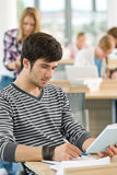 Male student writing notes in classroom Royalty Free Stock Photos