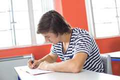 Male student writing notes in classroom. Portrait of male student writing notes in classroom Stock Photography