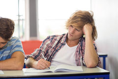 Male student writing notes in classroom. Portrait of male student writing notes in classroom Royalty Free Stock Photo