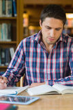 Male student writing notes at desk in the library Royalty Free Stock Photography