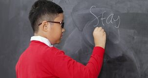 Male student writing Stay in School text. Male elementary school student writing Stay in School text on chalkboard and showing thumbs up, shot in 4k resolution stock footage