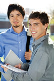 Male Students With Books Standing In University. Portrait happy male students with books standing in university campus Royalty Free Stock Photography