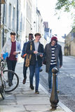 Male Students on a Break. A happy group of male students smile and laugh as they walk through the city together. They are carrying their bags and books Stock Photography