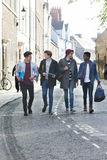 Male Students on a Break. A happy group of male students smile and laugh as they walk through the city together. They are carrying their bags and books Royalty Free Stock Photos