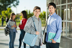 Male Students With Friends Standing In Background. Portrait of happy male students with friends standing in background on college campus Royalty Free Stock Images