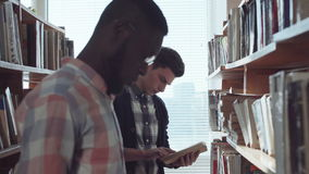 Male students looking for books in library stock footage