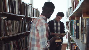 Male students looking for books in library stock video