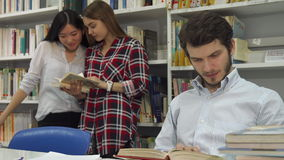 Male students reads the book at the library. Brunette male student reading the book at the library. Two girls standing near the book rack on background of stock video