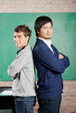 Male Students Standing Hands Folded Against. Side view portrait of young male students standing hands folded against greenboard in classroom Stock Photo
