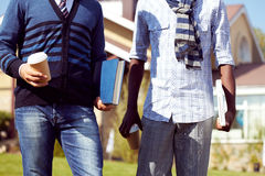 Male students. Torsos of two male students holding drinks and books Stock Image