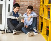 Male Students Using Digital Tablet While Sitting. Full length of young male students using digital tablet while sitting on floor in college library Stock Photos