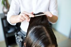 Male stylist hands combing wet hair at salon. Beauty, hairstyle and people concept - close up of male stylist hands combing wet hair at salon stock photo