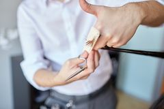 Male stylist hands cutting hair tips at salon. Beauty, hairstyle and people concept - male stylist hands with scissors and comb cutting hair tips at salon stock image