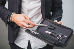 Male stylist is holding professional equipment. Focus on hands. Hairdresser is showing set of scissors in leather case Royalty Free Stock Image