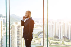 Male successful CEO is calling via cell telephone to his partner. Young man managing director having mobile phone conversation with client during break at job Royalty Free Stock Photography