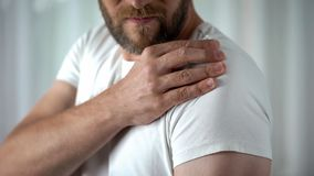Male suffering from shoulder ache, muscle pain, inflammation sprain problem. Stock photo stock photography