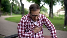 Male suffering sudden chest pain, sitting on bench in park, cardiology, health stock image