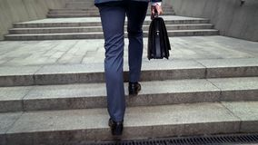 Male in suit holding leather briefcase climbing stairs to office building career royalty free stock photography