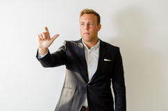 Male in suit pointing. Confident man in suit on white background Stock Image