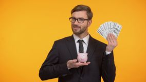 Male in suit showing piggy-bank and dollars, pension fund, retirement income