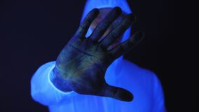 A male in a suit splattered with UV paint raises his hand in a stopping gesture.