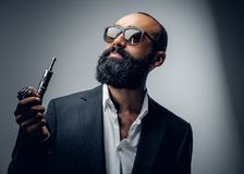 Male in a suit and sunglasses holding electronic pipe. Bearded male in a suit and sunglasses holding electronic pipe Royalty Free Stock Images