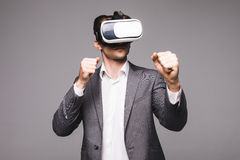 Male in a suit with virtual reality glasses on his head boxing isolated on grey background. Male in a suit with virtual reality glasses on his head. Isolated on Royalty Free Stock Photo