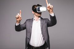Male in a suit with virtual reality glasses on his head isolated on grey background. Royalty Free Stock Photography