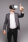 Male in a suit with virtual reality glasses on his head isolated on grey background. Stock Images