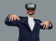 Male in a suit with virtual reality glasses on his head. Isolated on grey background Royalty Free Stock Photos